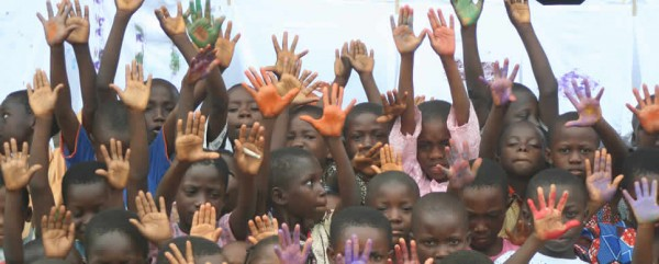 Students waving hands during art workshop in Ghana